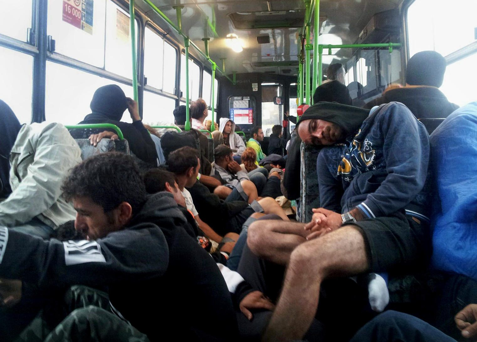 Exhausted refugees sleep on a bus to Vienna from Budapest. The bus was so crowded that Omar couldn't find a seat, and he crouched on the floor.